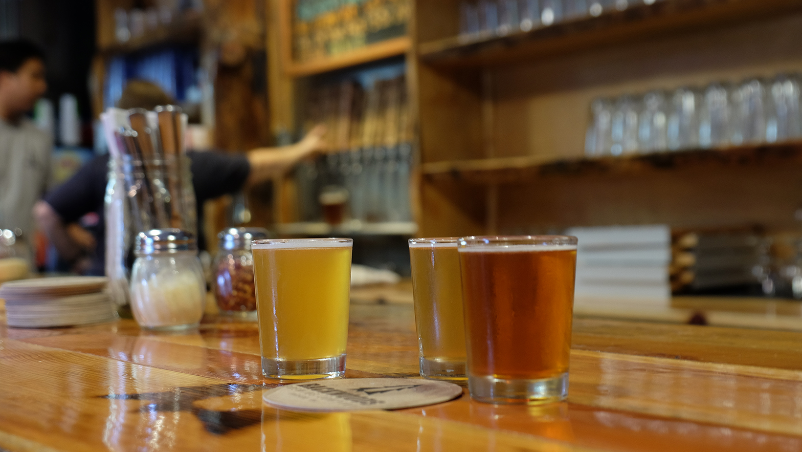 A natural wood bar with three craft beers and a bartender pouring taps at one of many tasty brew pubs in the Gorge