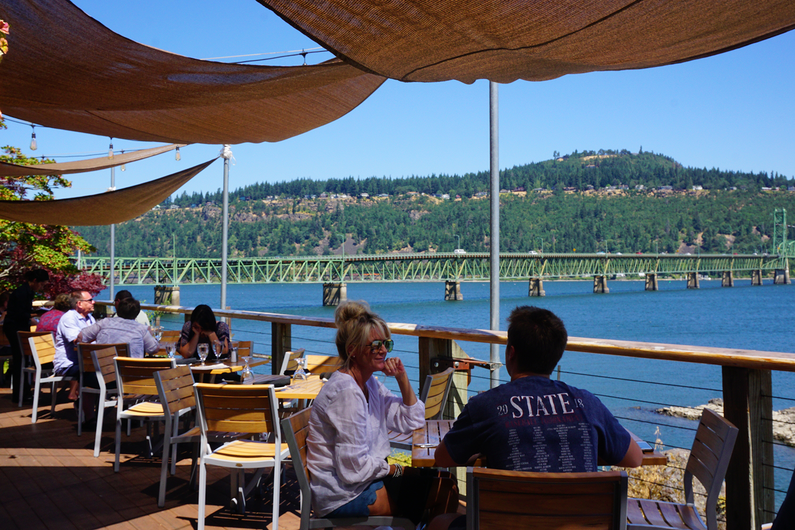 People enjoying a summertime waterfront meal with a view in Hood River