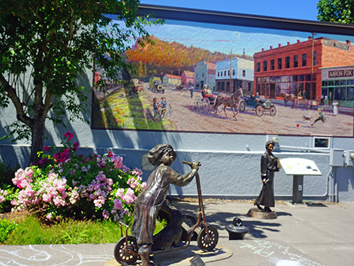 An historic painted mural of horse drawn carriage days accompanied by bronze sculptures