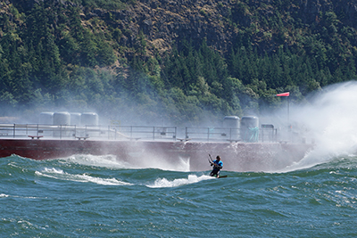 An adventurous kiteboarder gets the thrill of riding large waves and swells created by a nearby barge in the Gorge