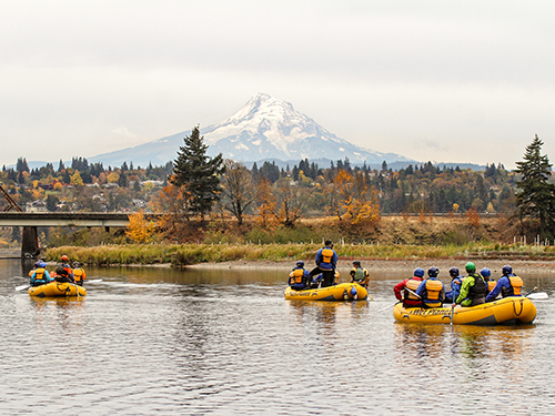 Three groups rafting in the Gorge on calm water as they approach Hood River with Mt. Hood in the background
