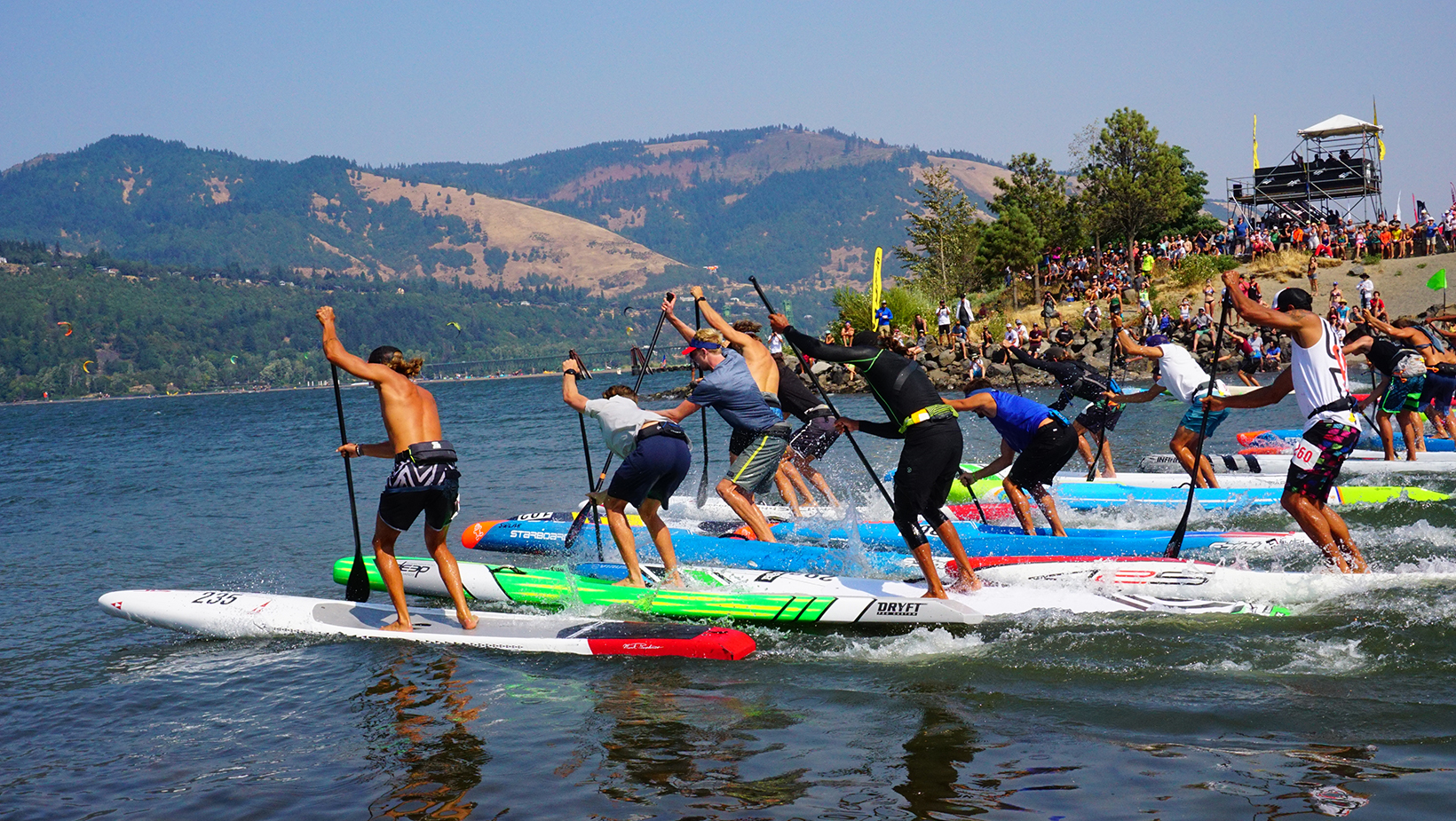 A stand up paddle race heads north across the Columbia River toward Washington as it departs the Hood River Waterfront