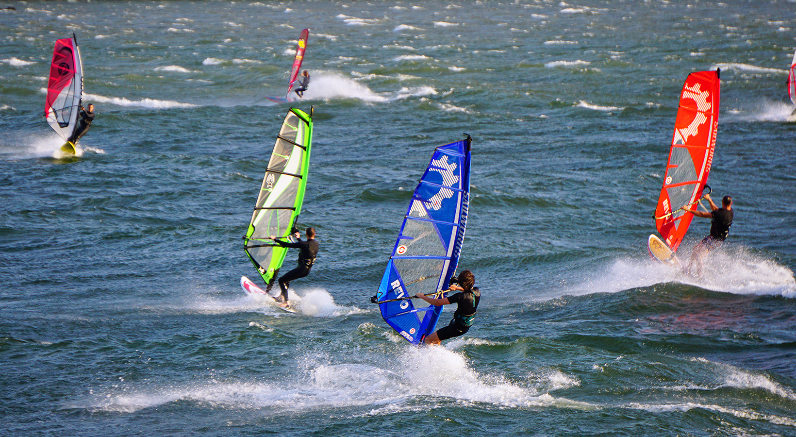 Windsurfers race across the Columbia River as the wind fills their sails and their boards zip through choppy waters