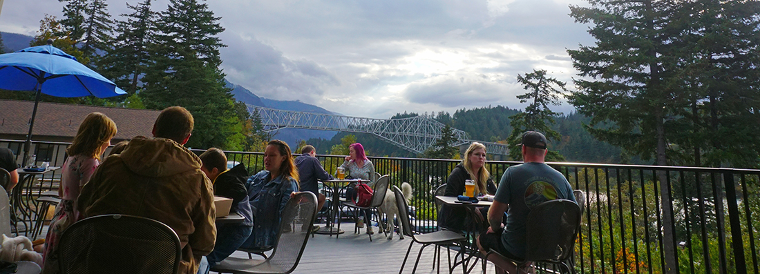 Outdoor dining in Cascade Locks, Oregon with a view of the Columbia River and Bridge of the Gods